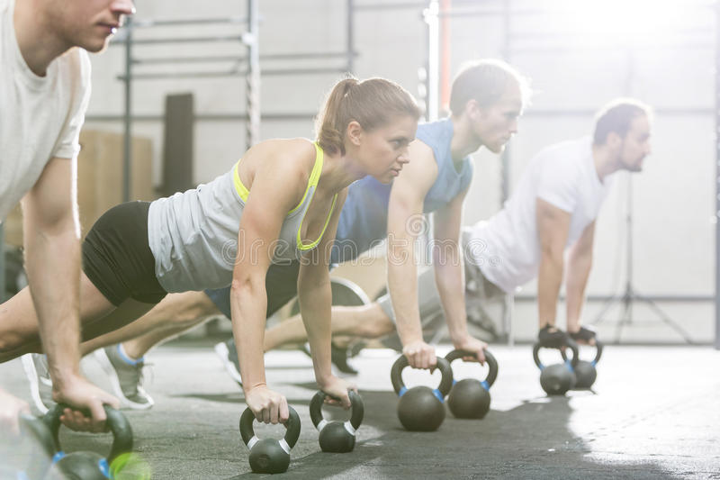 Determined people doing pushups with kettlebells at crossfit gym royalty free stock photography
