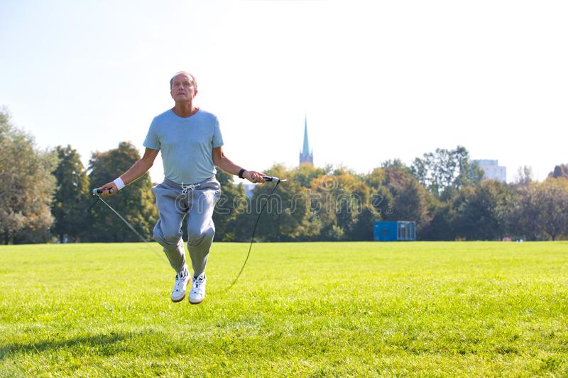 Determined senior man working out with skipping rope in park. Photo of Determined senior man working out with skipping rope in park royalty free stock photo