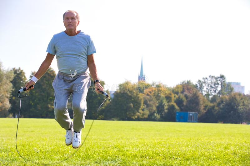 Determined senior man working out with skipping rope in park. Photo of Determined senior man working out with skipping rope in park royalty free stock photography