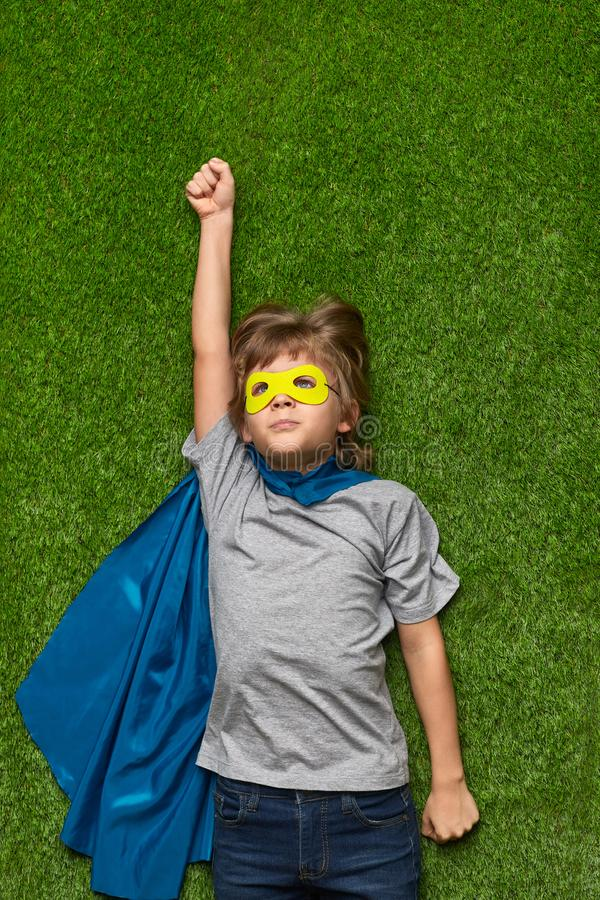 Determined superhero flying up. From above concentrated little boy in superhero costume pretending to fly up while lying on green grass stock photos