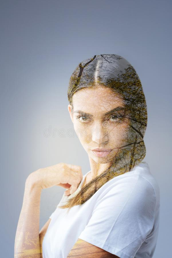Determined thoughtful woman magnifying with her look. Dare you. Irresistible beautiful nice woman posing on the grey background while touching her shirt and stock photos