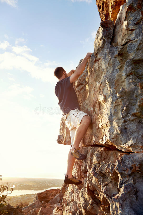 Determined to get to the top. Rockclimber climbing up a steep piece of mountain with copyspace royalty free stock image