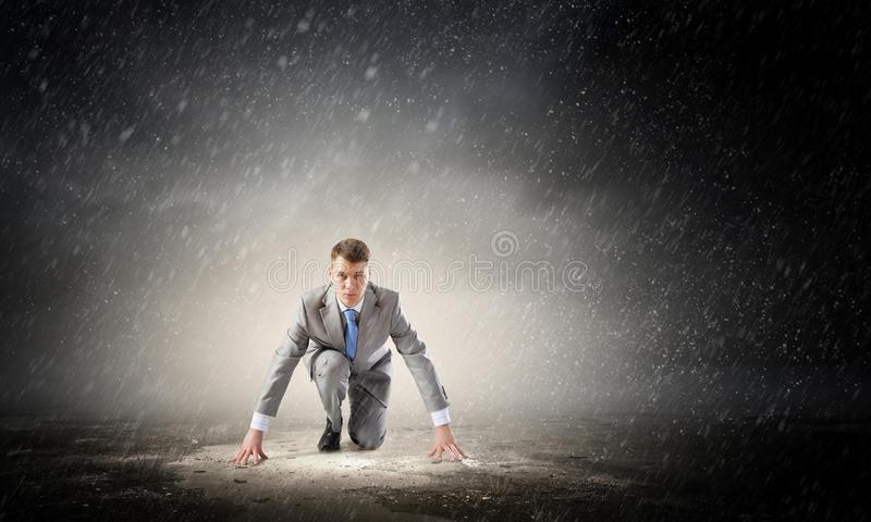 He is determined to start now . Mixed media. Young businessman in start pose outdoor ready to run royalty free stock images