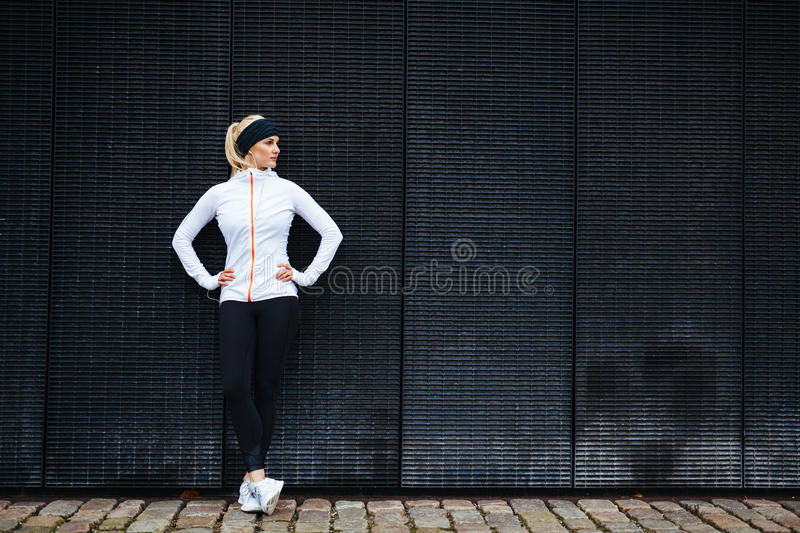 Determined woman resting after jogging in the city. Full length shot of sporty young woman relaxing after running exercise stock image