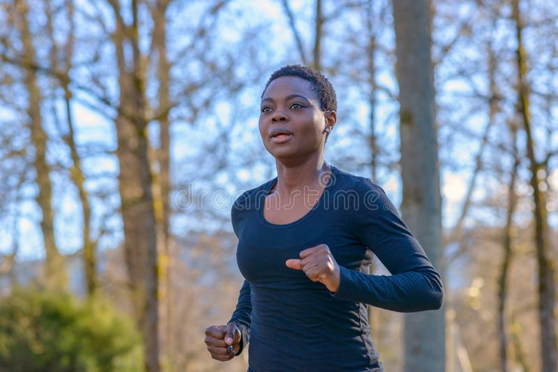 Determined young African woman training in a park royalty free stock images