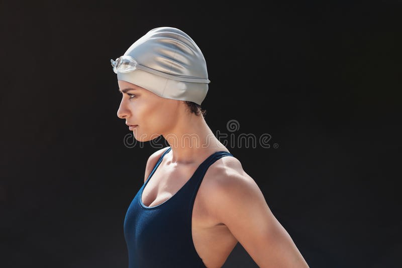 Determined young female swimmer. Side portrait of determined young female swimmer on black background. Young woman in swimming costume looking away royalty free stock photos