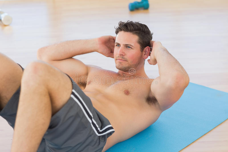 Determined young man doing abdominal crunches royalty free stock image