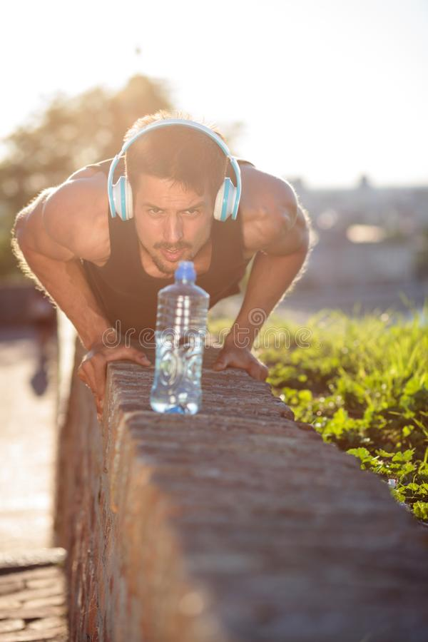 Determined young man doing push-ups. Front view stock image