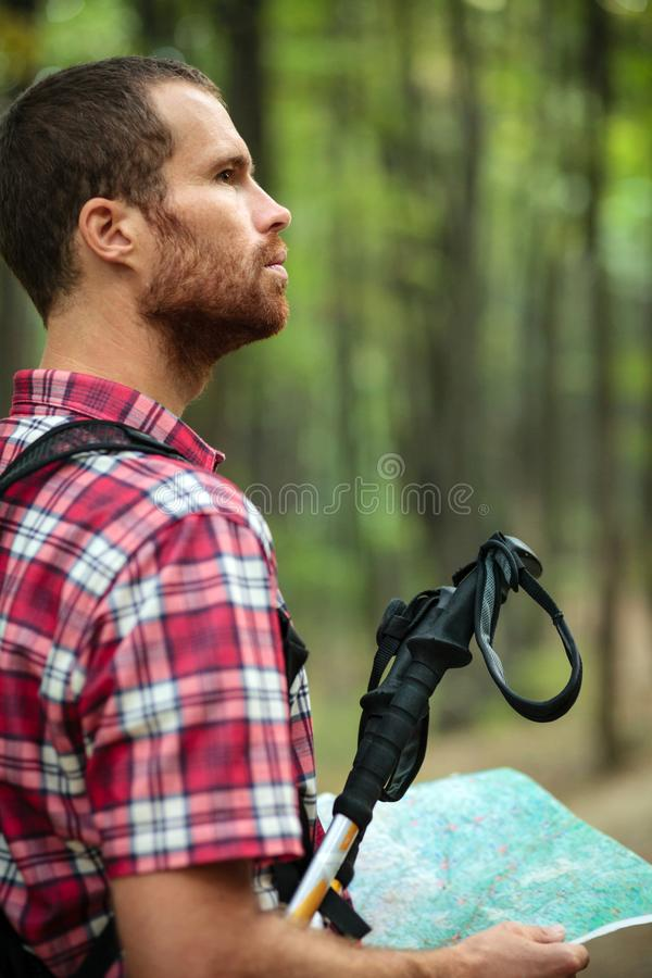 Determined young man hiking through lush green forest, holding a map and navigating royalty free stock image