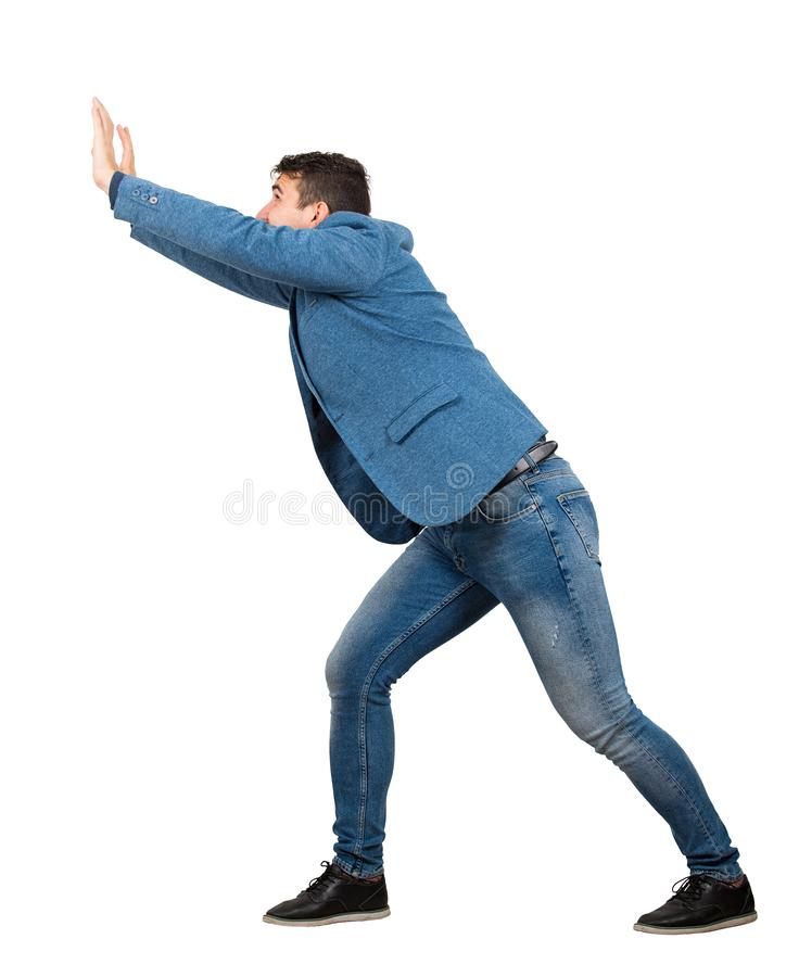 Determined young manmaking effort as pushing an heavy invisible object isolated on white background. Confident guy, difficult task stock photography