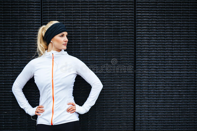Determined young sports woman. Portrait of determined young sports woman looking away while standing against a dark wall outdoors stock image