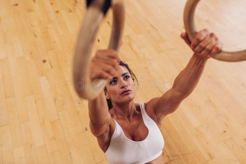 Determined young woman at gym using gymnastic rings royalty free stock photo