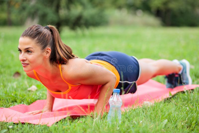 Determined young woman holding plank position on exercise mat. Determined young woman exercising in a park. Holding plank position on exercise mat. Keeping fit stock photography