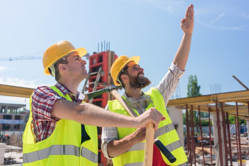 Determined young worker pointing up while imagining the height of a building stock photography