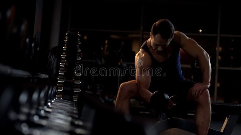 Determinować bodybuilder robi posadzonemu dumbbell kędziorowi, wieczór trening fotografia stock