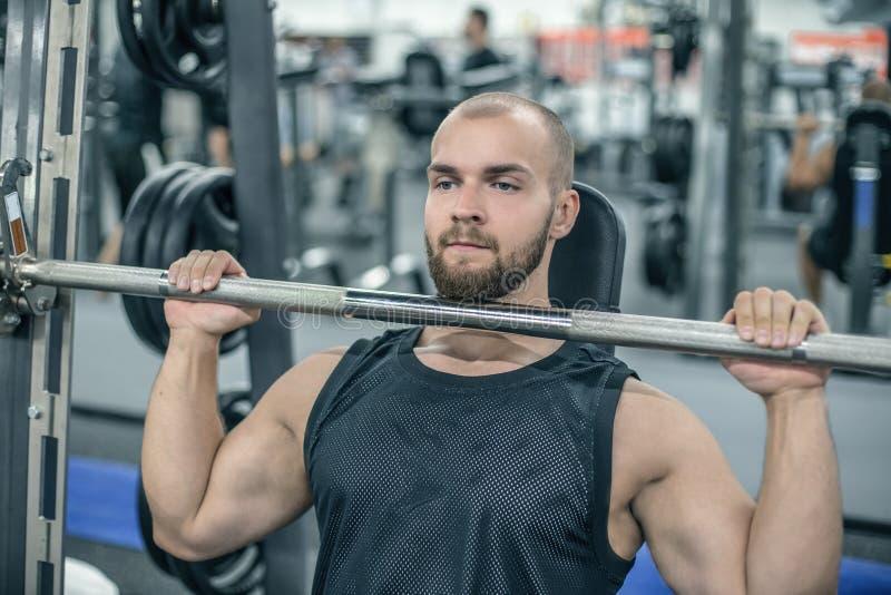 Determinować młody człowiek sprawności fizycznej model angażował z barbell w Smith symulancie w gym Pojęcie silni mięśnie i napię obrazy stock