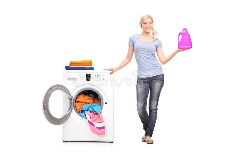 Detersivo della tenuta della donna accanto ad una lavatrice immagini stock