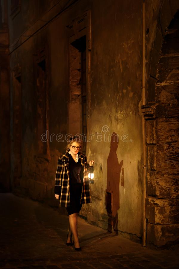 Detetive fêmea louro bonito com a lanterna do vintage em retro fotografia de stock royalty free