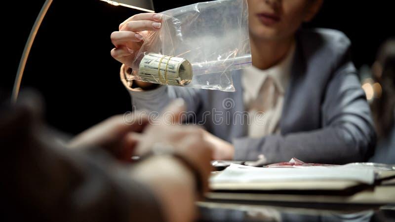 Detetive fêmea que mostra o dinheiro do dinheiro ao suspeito, interrogação do traficante de drogas fotos de stock