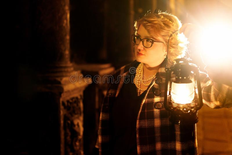 Detetive louro bonito da mulher no revestimento retro à moda que guarda o foto de stock