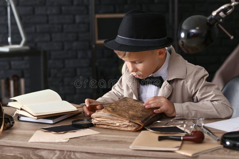 Detetive pequeno bonito que lê o livro velho dentro fotografia de stock