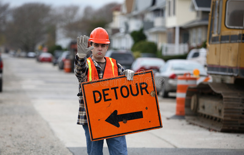 Detour. Road construction worker holding a detour sign and gesturing to stop