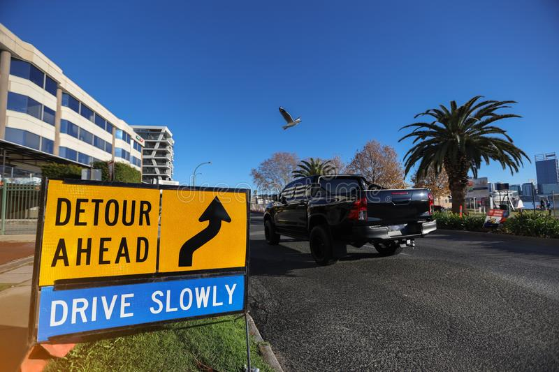Detour drive slowly ahead safety warning sign applying on public busy residential areas. Yellow board with black whiting detour safety warning sign ahead drive stock image