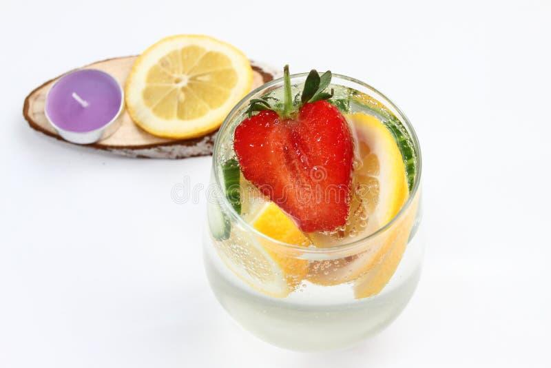 Detox bracht water met citroen, komkommer en aardbei op witte achtergrond met decoratie op smaak Gezond voedselconcept Verfrissen stock fotografie