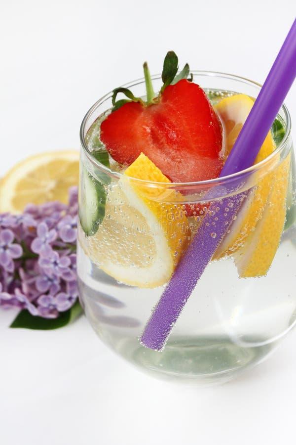 Detox bracht water met citroen, komkommer en aardbei op witte achtergrond met lilac en houten decoratie op smaak Gezond voedselco stock foto