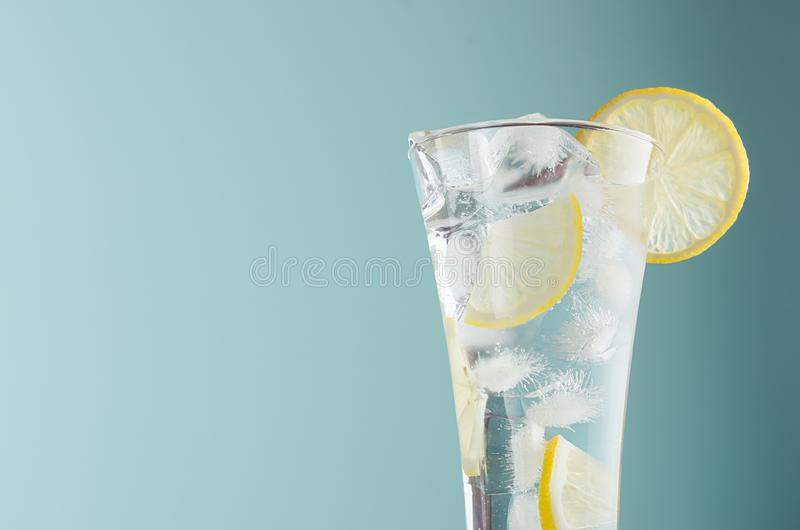 Detox citrus drink with lemon slices, ice cubes, sparkling water in misted glass in modern mint color background, closeup, edge. stock image