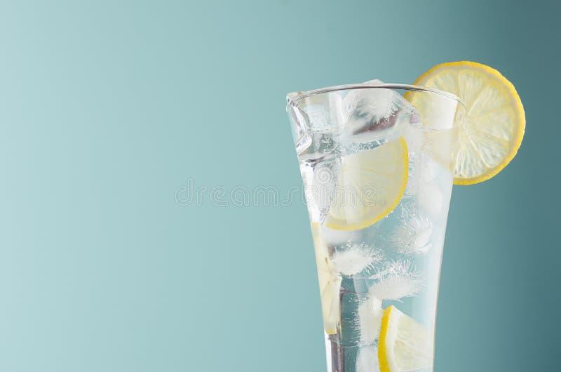 Detox cytrusa napój z cytryna plasterkami, kostka lodu, iskrzasta woda w zaparowywającym szkle w nowożytnym nowym koloru tle, zbl obraz stock