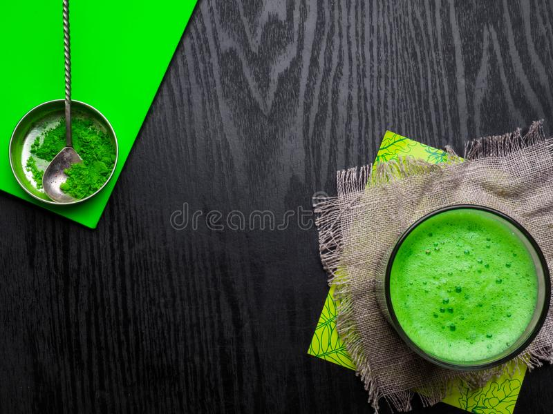Detox drink as Japanese matcha green powdered tea, latte served in glass on sackcloth, powder in bowl with vintage spoon, copy. Japanese matcha green powdered stock photography