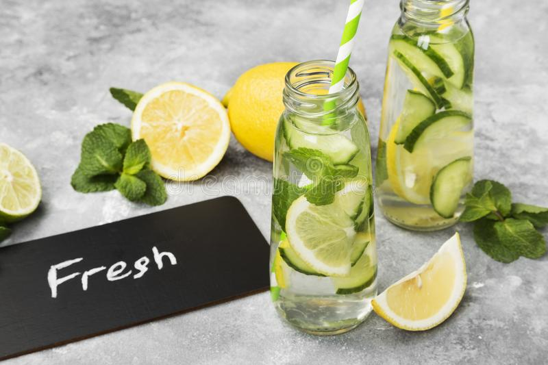 Detox drink with cucumber, lemon and mint on gray background.  royalty free stock photography