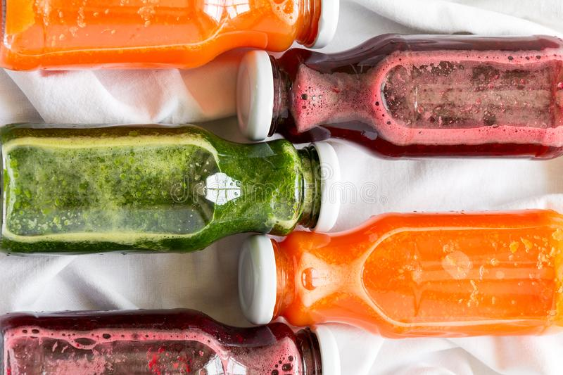 Detox drinks in bottles: fresh smoothies from vegetables: beet, carrot, spinach, cucumber and apple. On white background stock photography