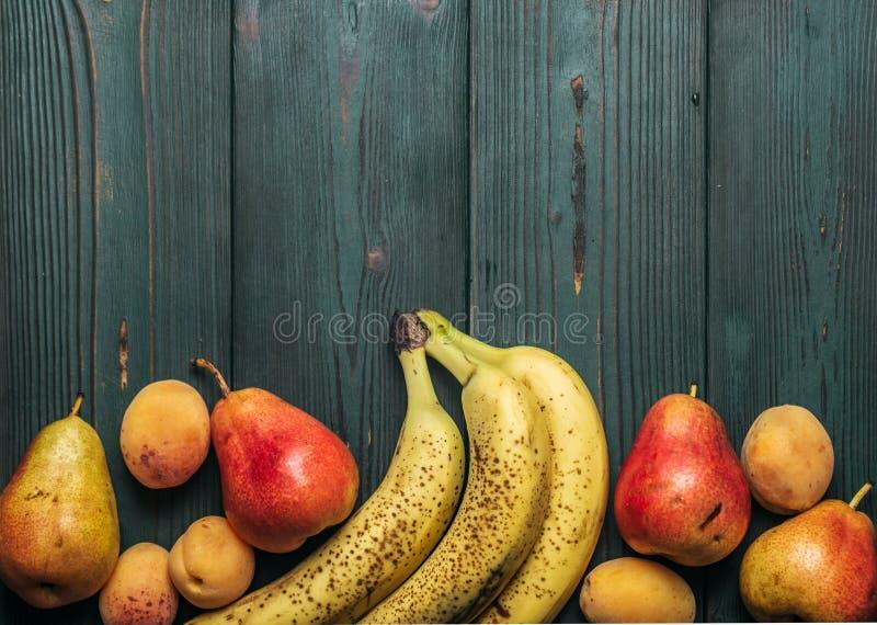 Detox: ein Zerstreuen von frischen reifen Bananen, von Birnen und von Aprikosen auf einer hölzernen grünen Tabelle Kopieren Sie P stockfotografie