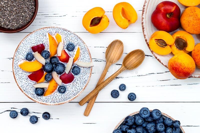 Detox en gezond de komconcept van het superfoodsontbijt De pudding van chiazaden van de veganistkokosmelk over rustieke lijst met stock fotografie