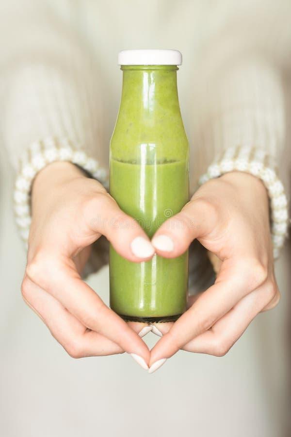 Detox estacional de la bebida del smoothie del invierno Muchacha en un suéter de lana, sosteniendo una botella de smoothies verde fotos de archivo