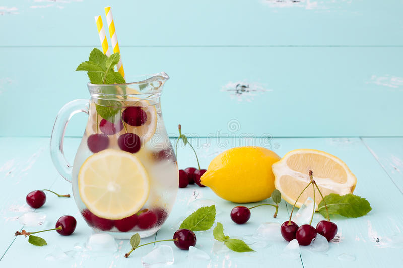 Detox fruit infused flavored water with cherry, lemon and mint royalty free stock photography