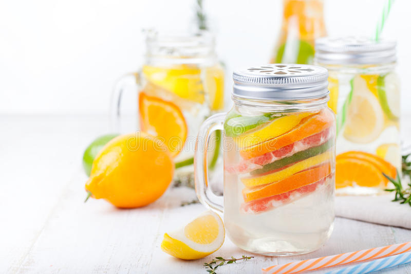 Detox fruit infused flavored water. Refreshing summer homemade lemonade cocktail. Cleanse body and burn fat stock photos