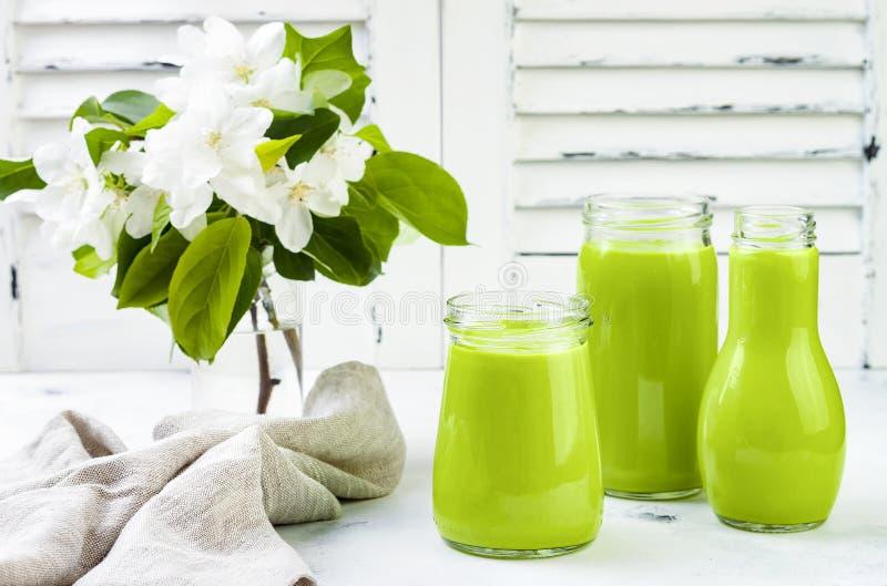 Detox, gezonde groene smoothie in kruiken en fles Witte houten rustieke achtergrond met appelbloesem stock fotografie