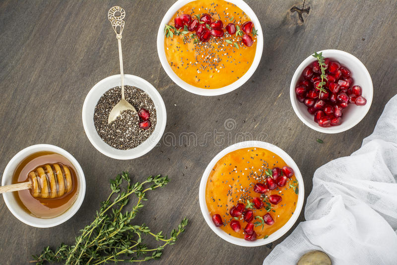 Detox and healthy breakfast smoothie of ripe juicy fruits persimmon, pomegranate seeds, chia with honey thyme on a. Detox and healthy breakfast smoothie of ripe stock photo