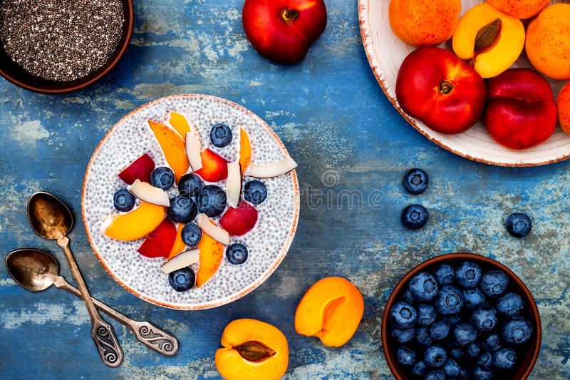 Detox and healthy superfoods breakfast bowl concept. Vegan coconut milk chia seeds pudding over rustic table with various fruits stock photography