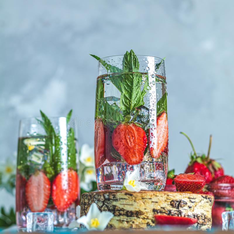 Detox infused water with strawberry and mint. In highball glasses on blue concrete table background, copy space. Cold summer drink. Mineral water royalty free stock photos