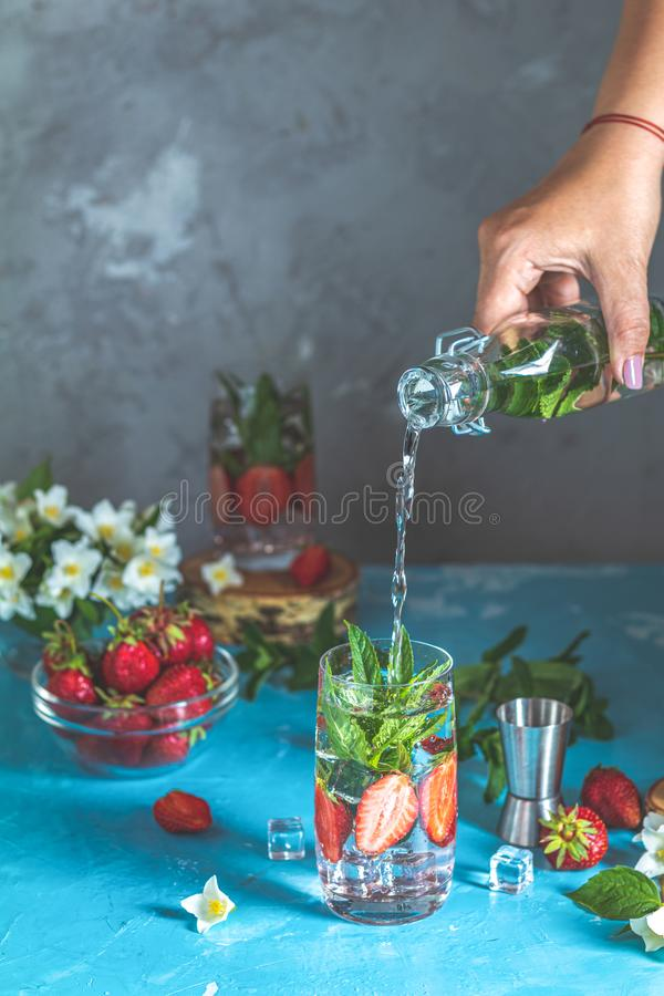 Detox infused water with strawberry and mint in highball glasses. Woman pouring lemonade from bottle into glass. Detox infused water with strawberry and mint in stock image