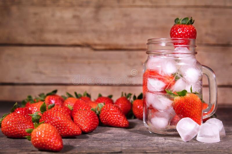 Detox o agua infundida con las fresas, limonada fresca con el ic imagen de archivo