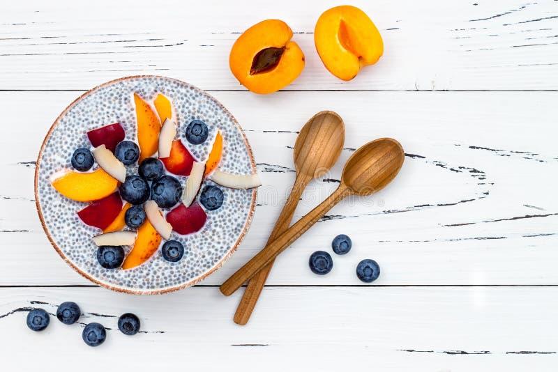 Detox och sunt begrepp för superfoodsfrukostbunke Strikt vegetariankokosnöten mjölkar chiafröpudding över den lantliga tabellen m