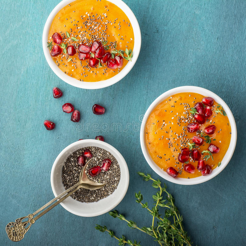 Detox pomarańczowi zdrowi śniadaniowi smoothies z sezonową dojrzałą owoc, chia ziarna, granatowiec na jaskrawy barwionym fotografia stock