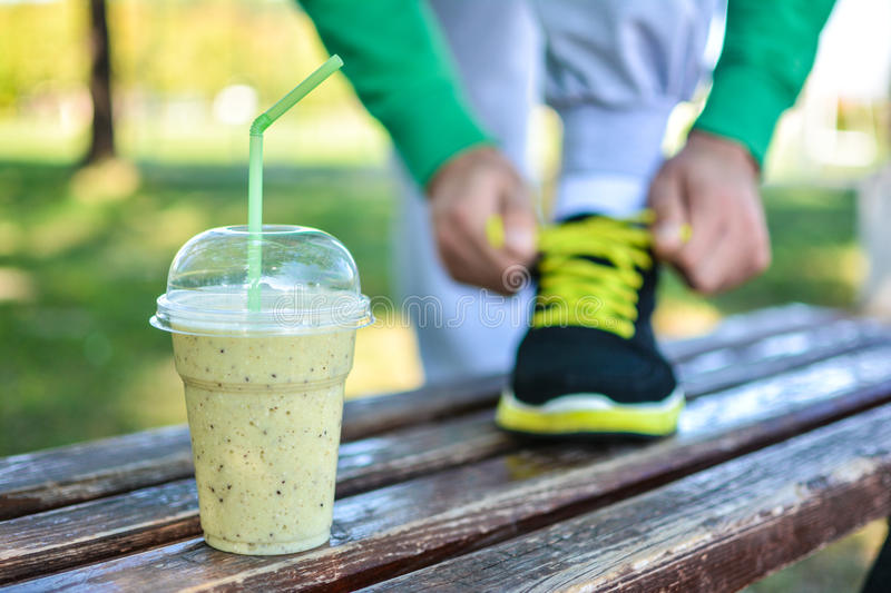 Detox smoothie drink and running footwear close up. Man athlete tying sport shoes. stock photo