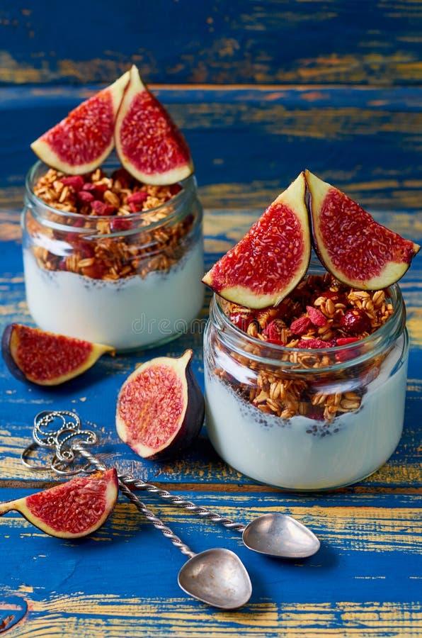 Detox superfoods ontbijt of gezond dessert - de pudding van de chiamelk met granola en verse fig. in de glaskruiken op de blauwe  royalty-vrije stock foto's