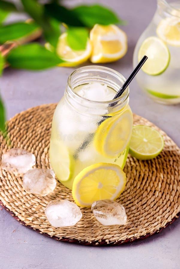 Detox-Wasser mit Zitrone amd Kalk und geschmackvolles Sommer-Limonaden-Getränk mit Eis-Würfel Detox-gesunder Getränk-Vertikale ge stockbild